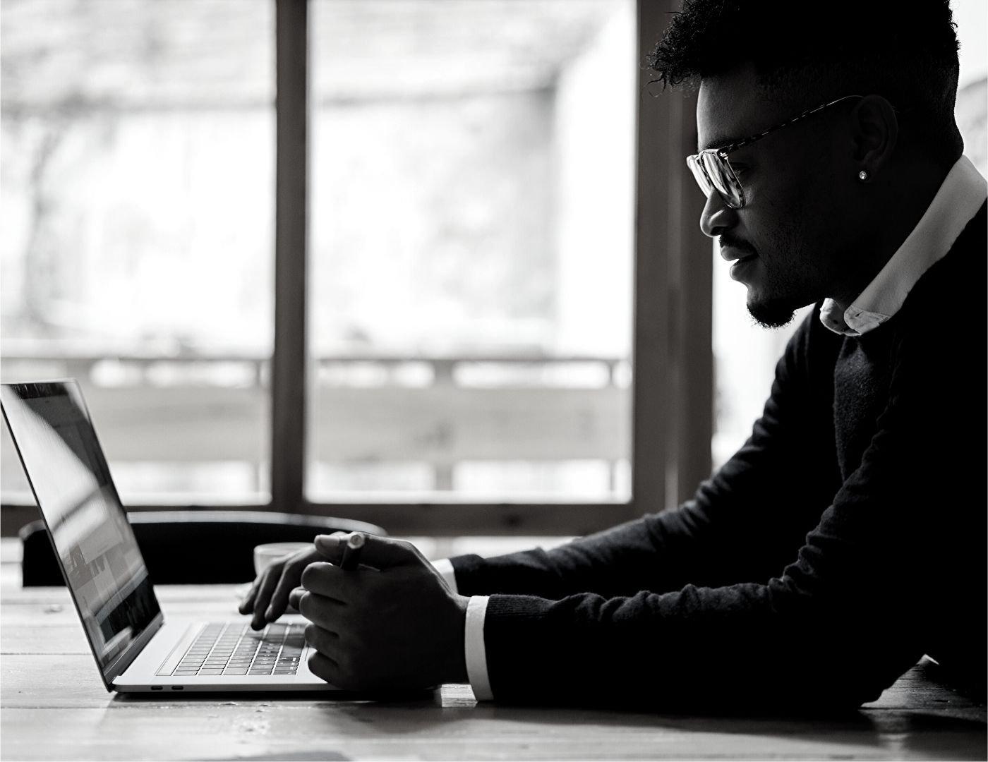 Man On Laptop On Table Near Window