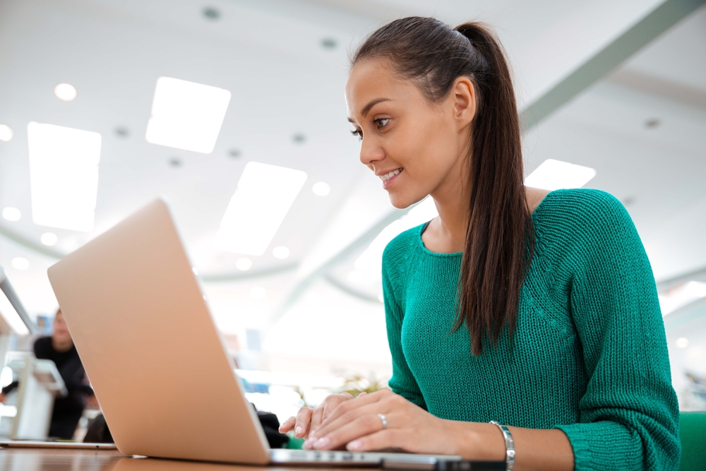 Portrait of a happy female student using laptop computer in university-1